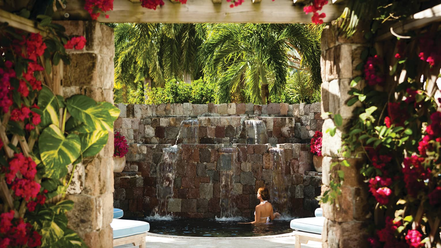 Woman bathes in small pool under stone fountain under palm trees, brick walls with pink flowers