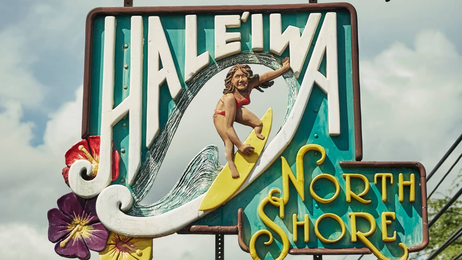 Colourful wood sign reading Haleiwa North Shore with carving of woman on surfboard