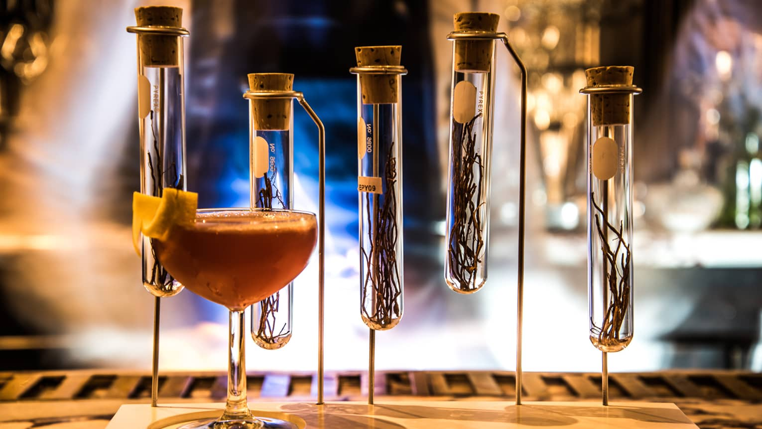 Cocktail on bar in front of test tubes with spices