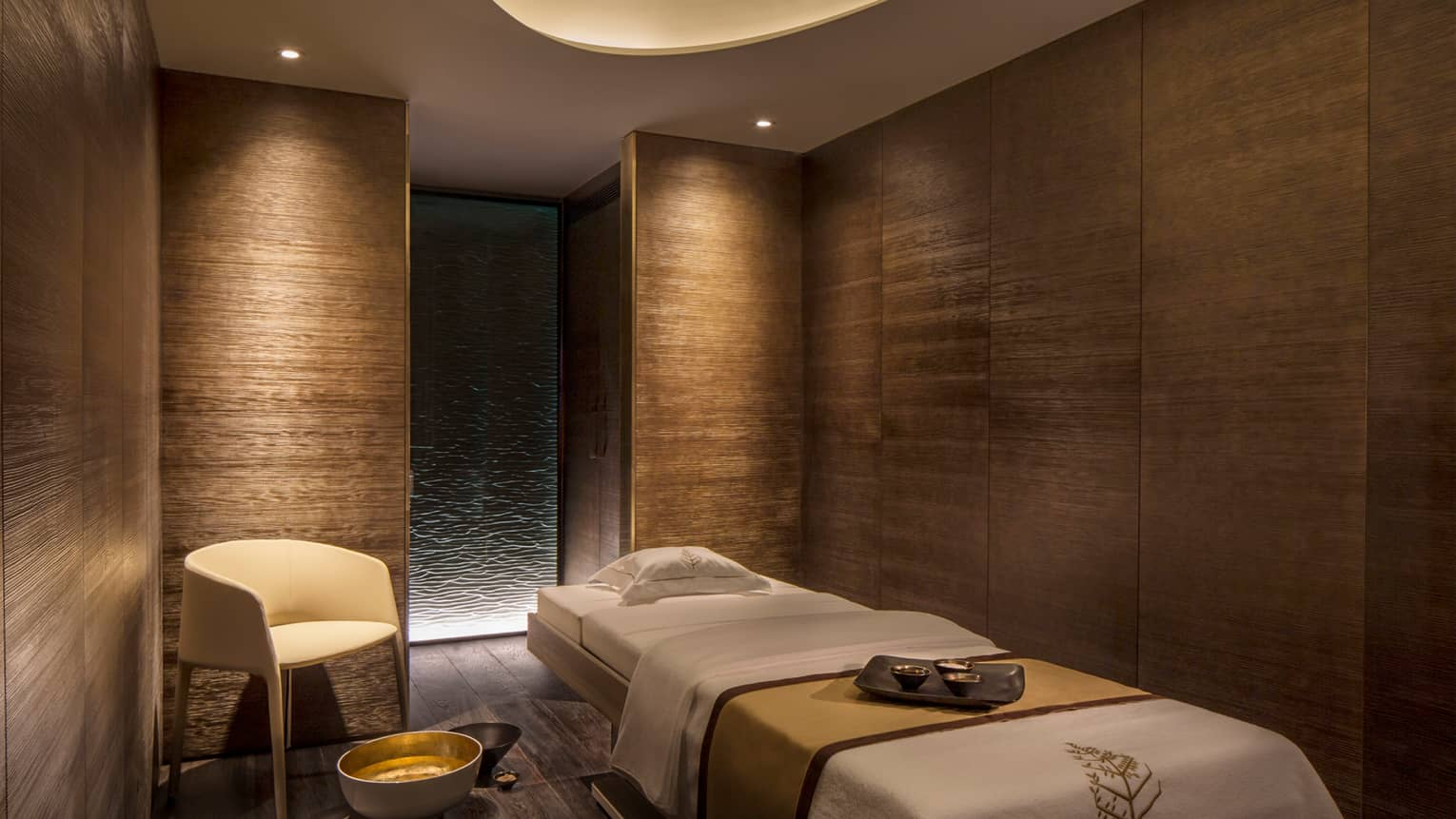 View of private massage room in spa and wellness centre, wood grain walls and low lighting
