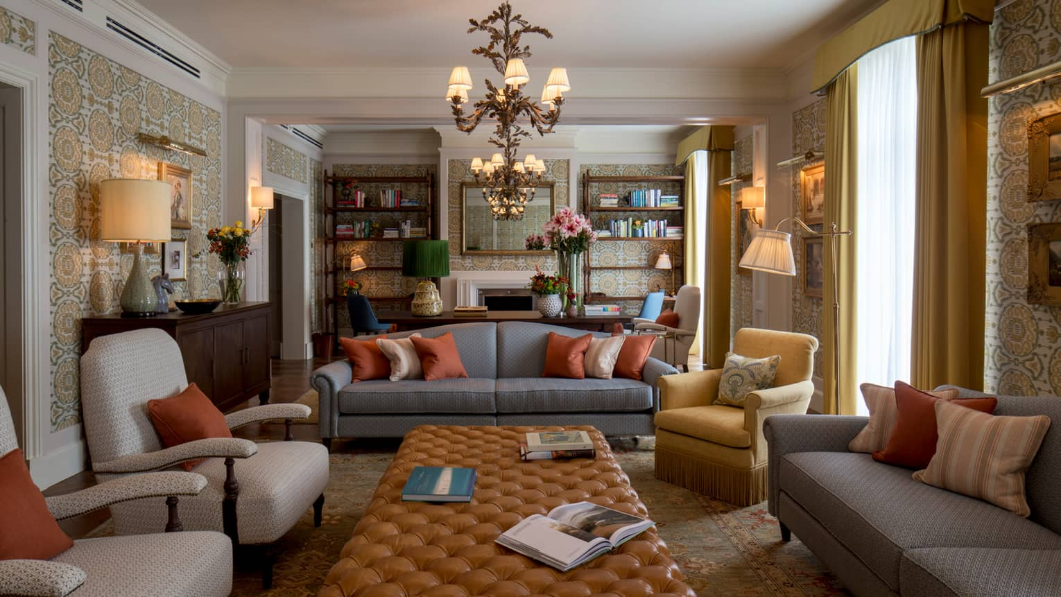 Royal Suite sofas, chairs around long tufted leather bench under chandeliers, bookshelves
