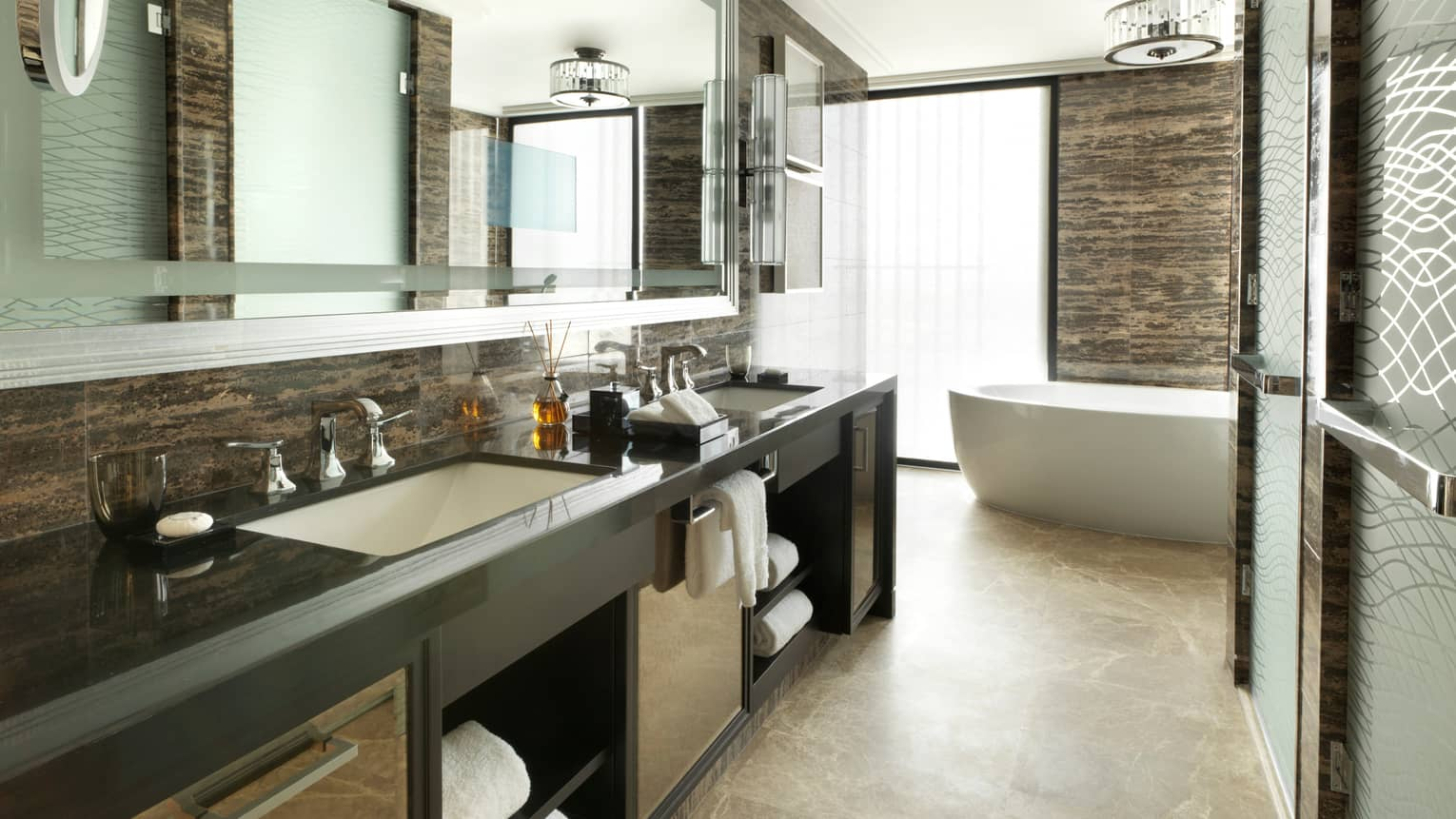 Premier Four Seasons Executive Suite large bathroom with double vanity sinks, glass shower, white soaker tub