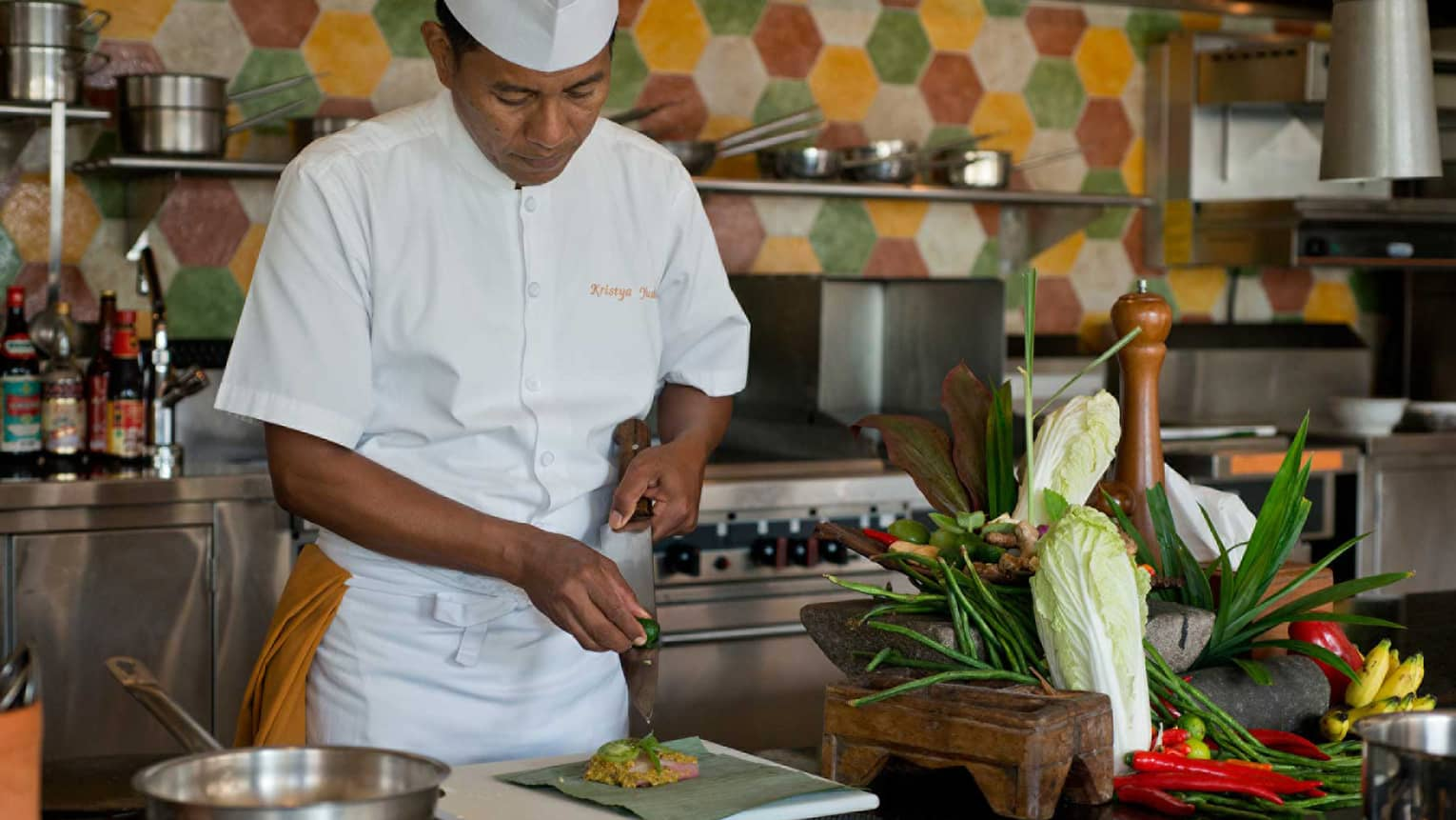Chef in white uniform squeezes lime on large kitchen knife over dish, next to heads of fresh lettuce and whole peppers
