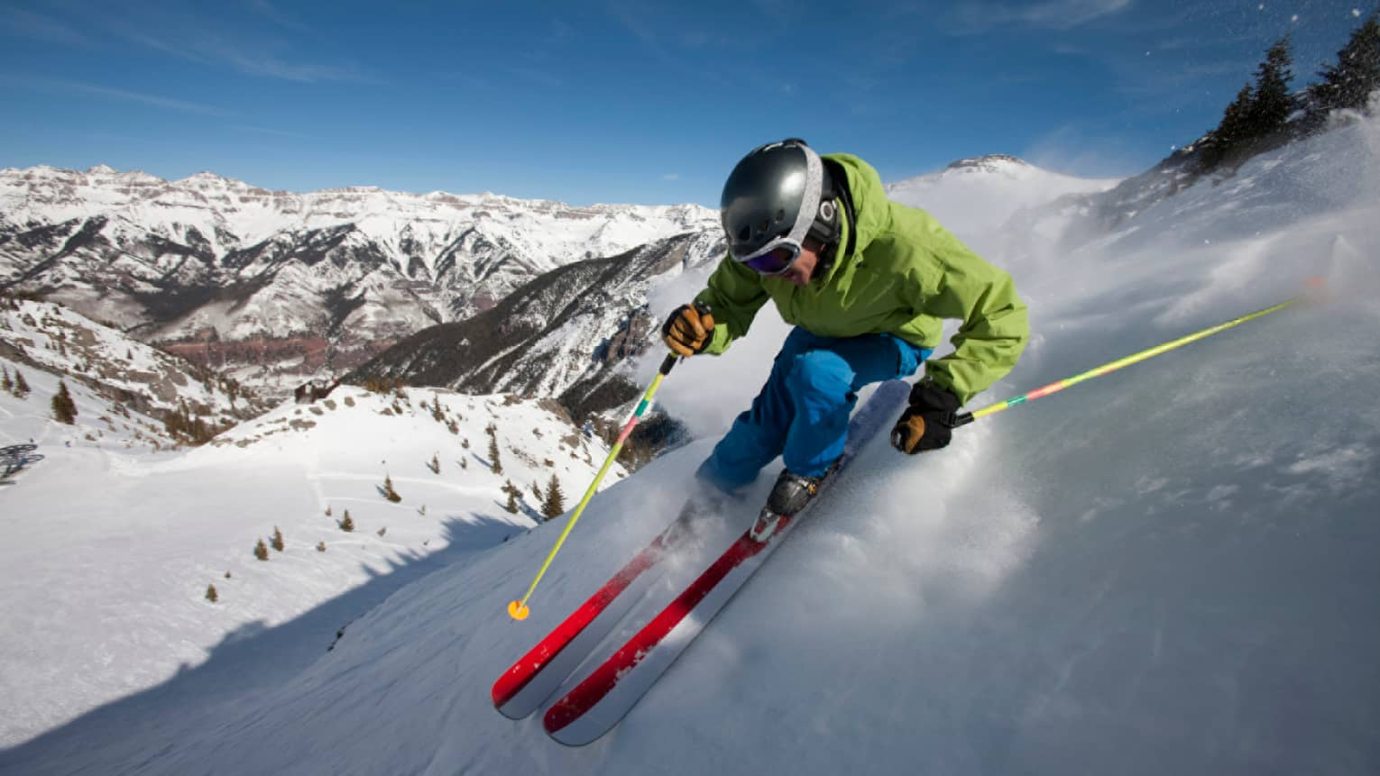 Man in colourful ski jacket, helmet, holds poles, skis down Rocky Mountain
