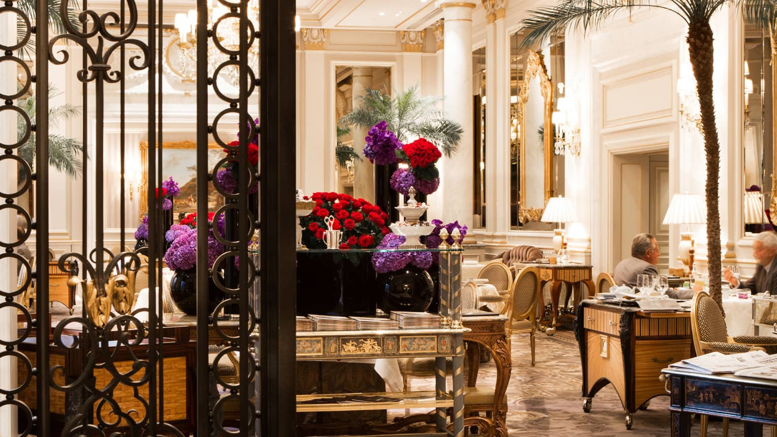 Le Cinq dining room, decorative wrought iron gate, red, purple flowers on gold tables