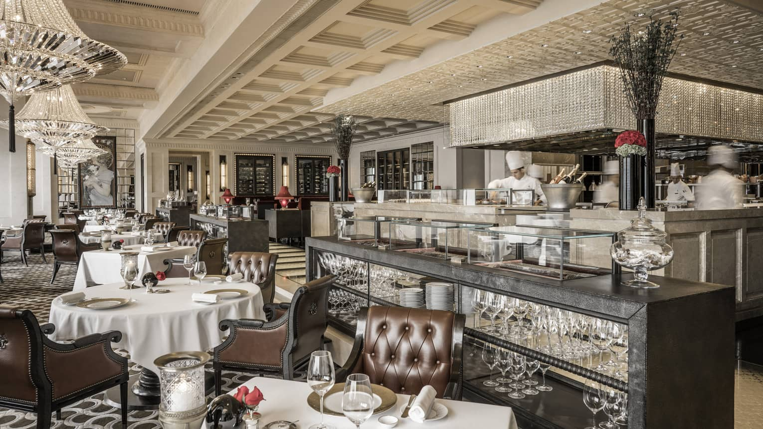 Contemporary chinoiserie dining room tables, leather chairs, chefs behind marble counter with crystal overhang