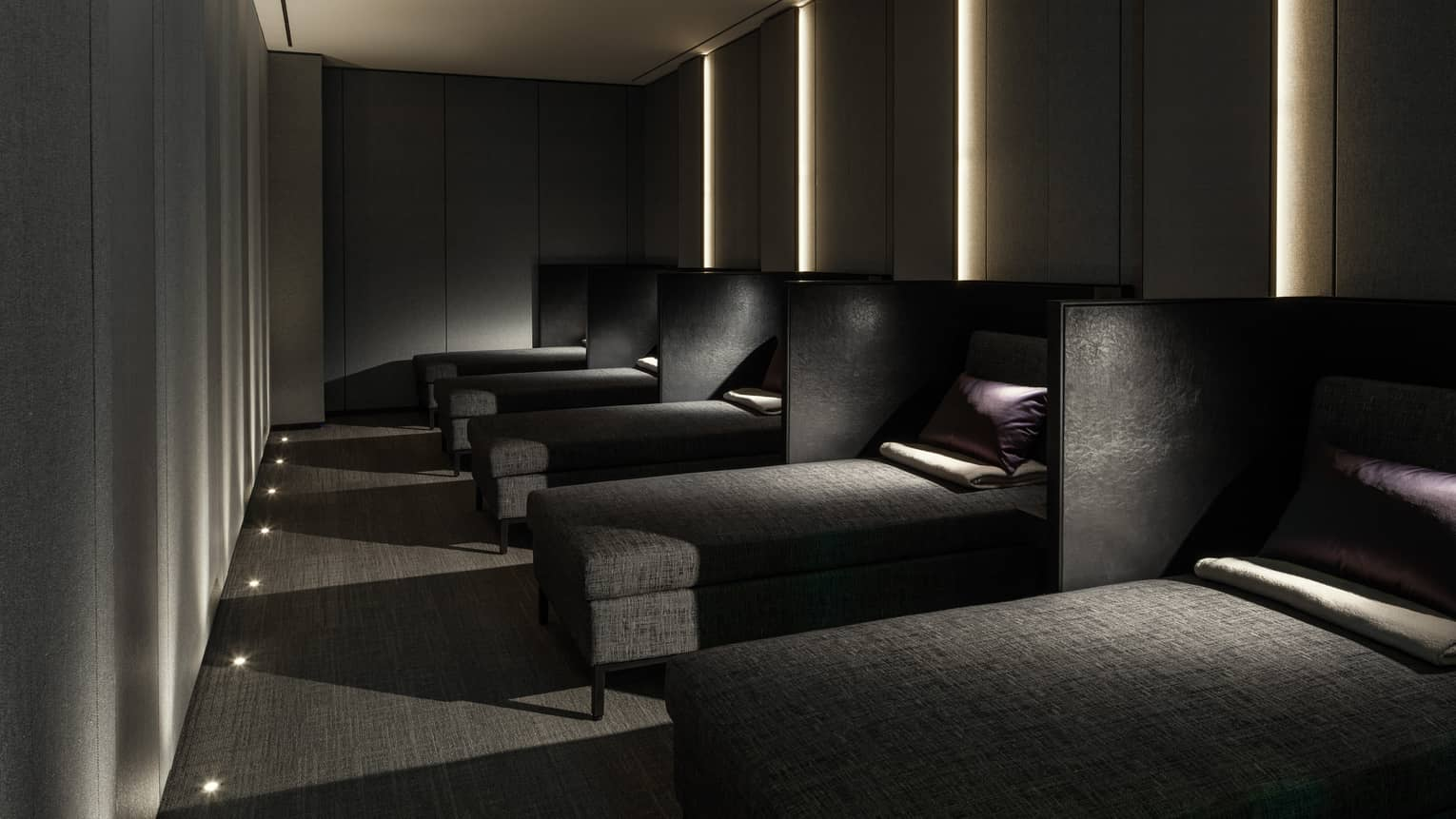 Row of lounge chaises with pillows, blankets in dark Napping Room