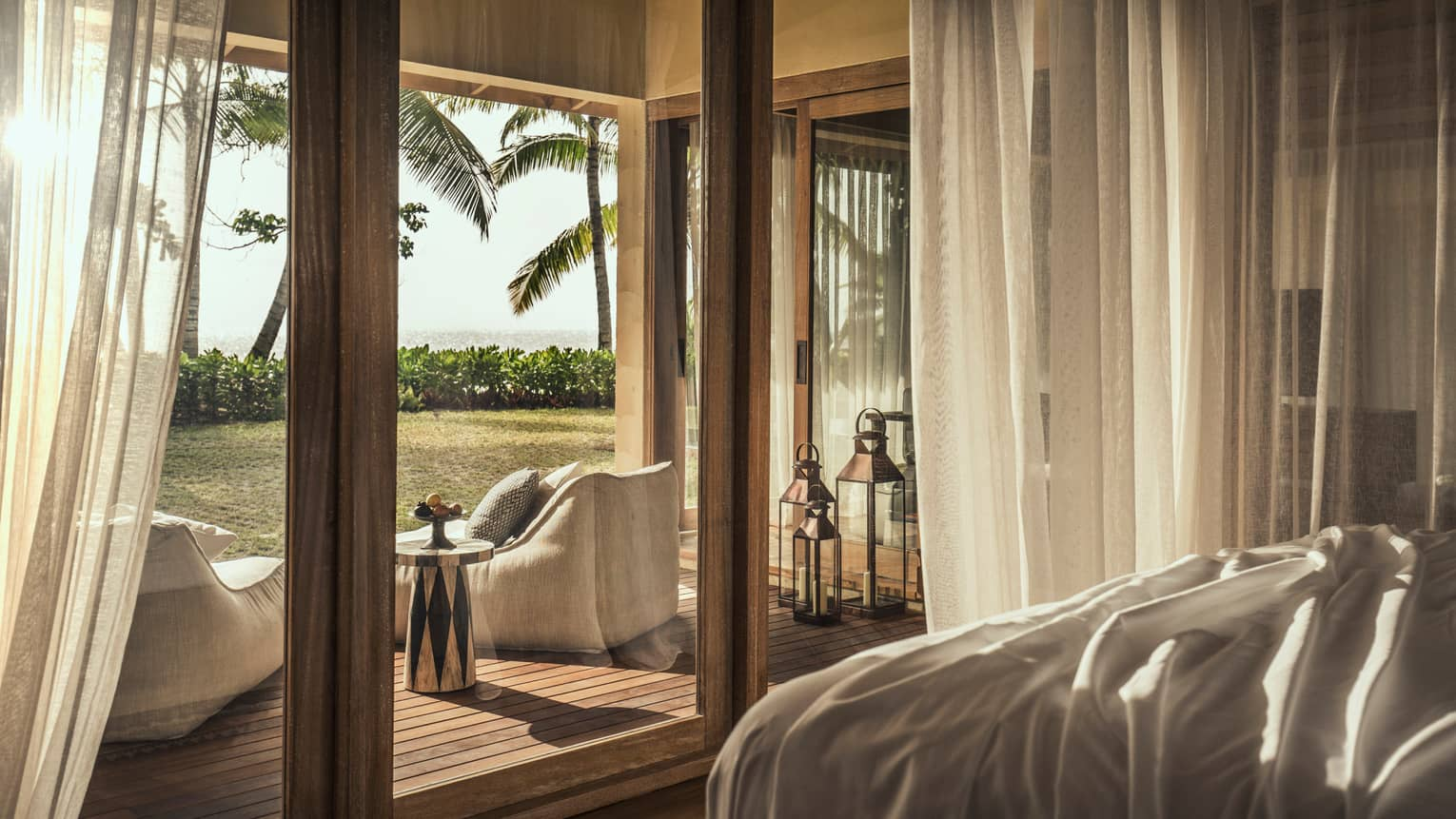 Desroches Suite bedroom floor-to-ceiling glass patio doors, cushioned chairs on deck