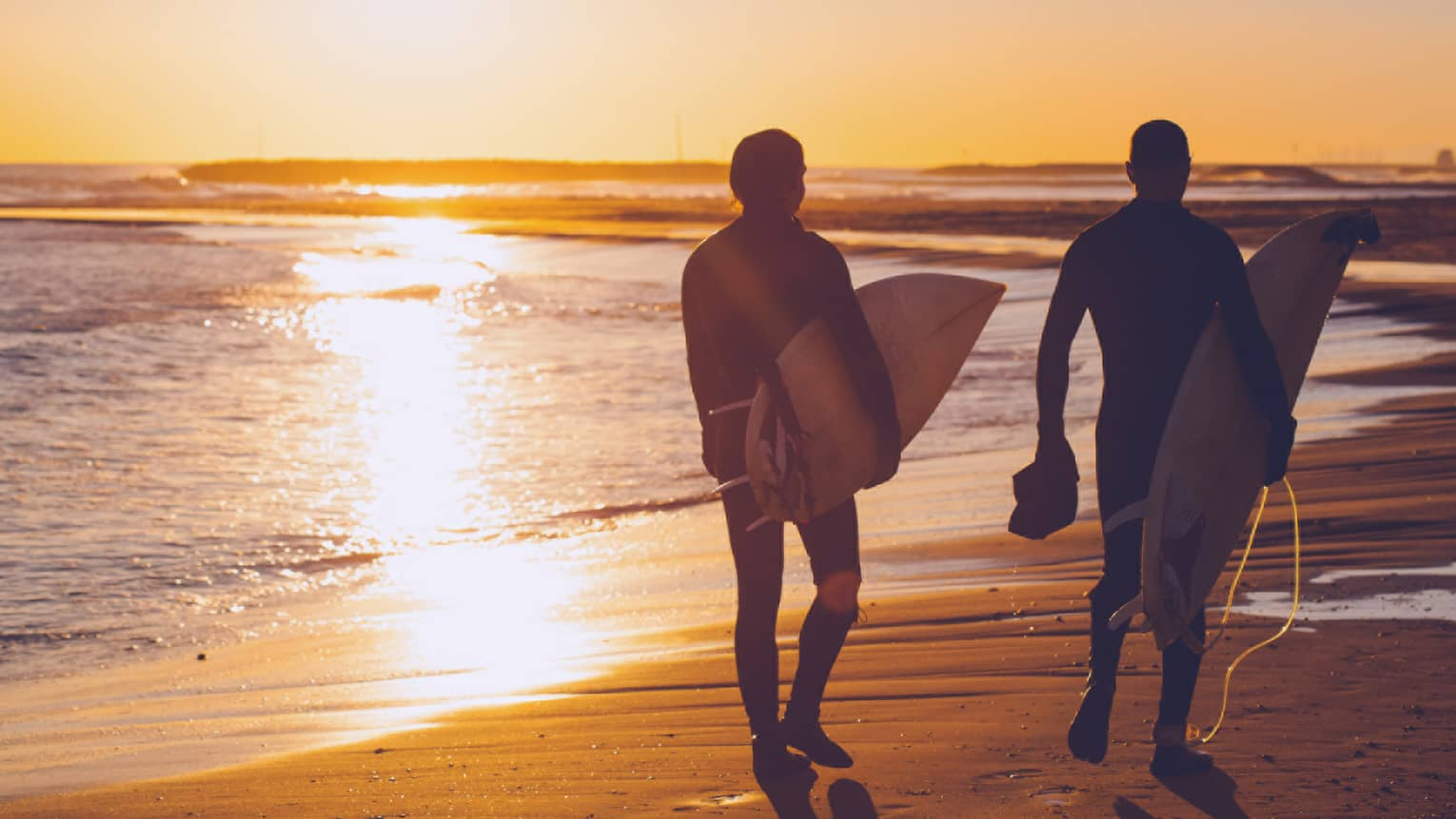 Silhouettes of two people carrying surfboards across beach at sunset