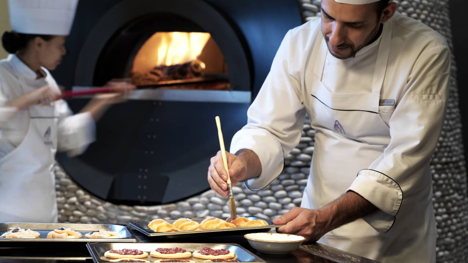 Chef in white uniform, apron brushes pastries in front of wood-burning oven