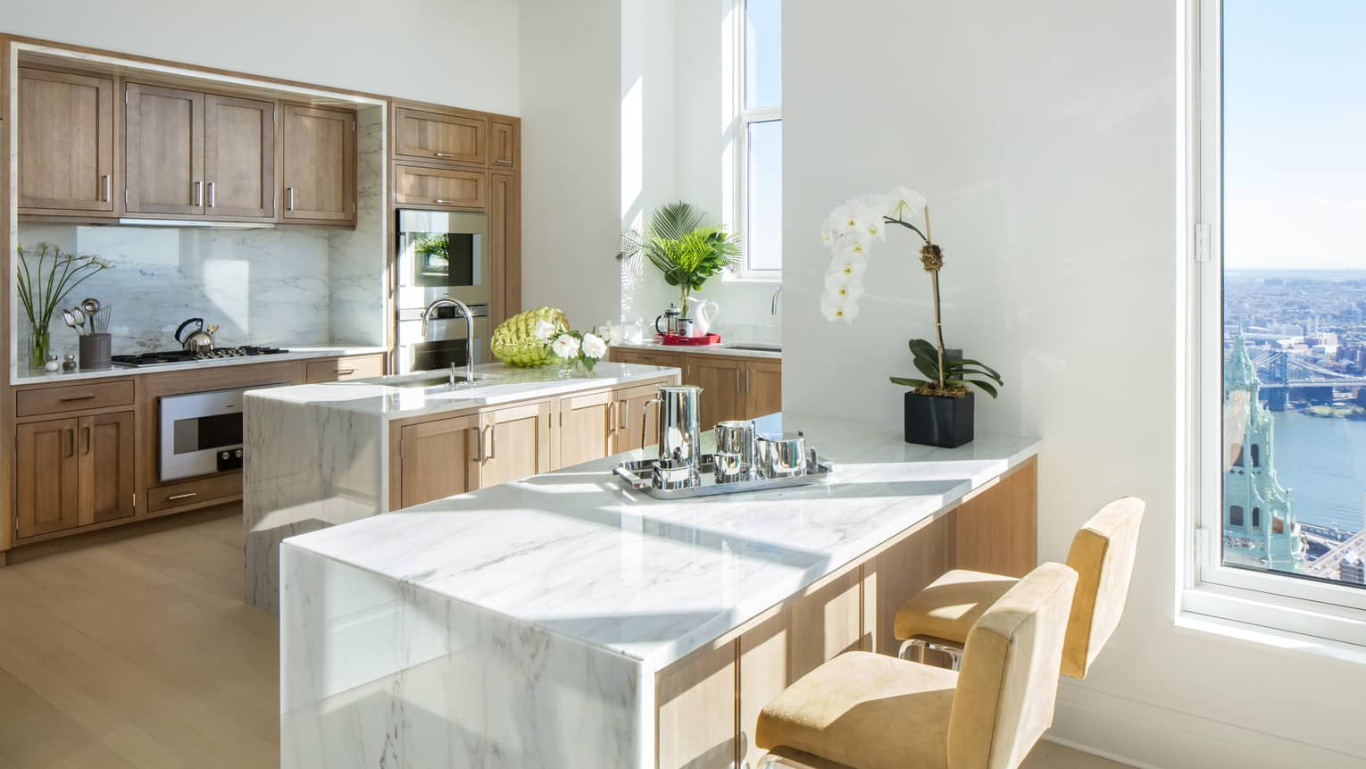 Kitchen island with Colorado White marble countertops and stools, solid oak cabinets, fresh white orchids