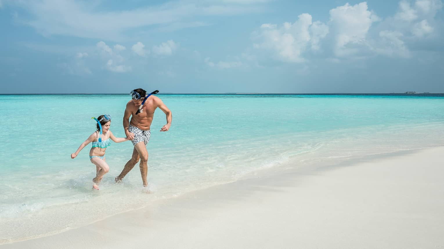 Man, young girl wearing snorkelling mask walk from blue lagoon to white sand beach