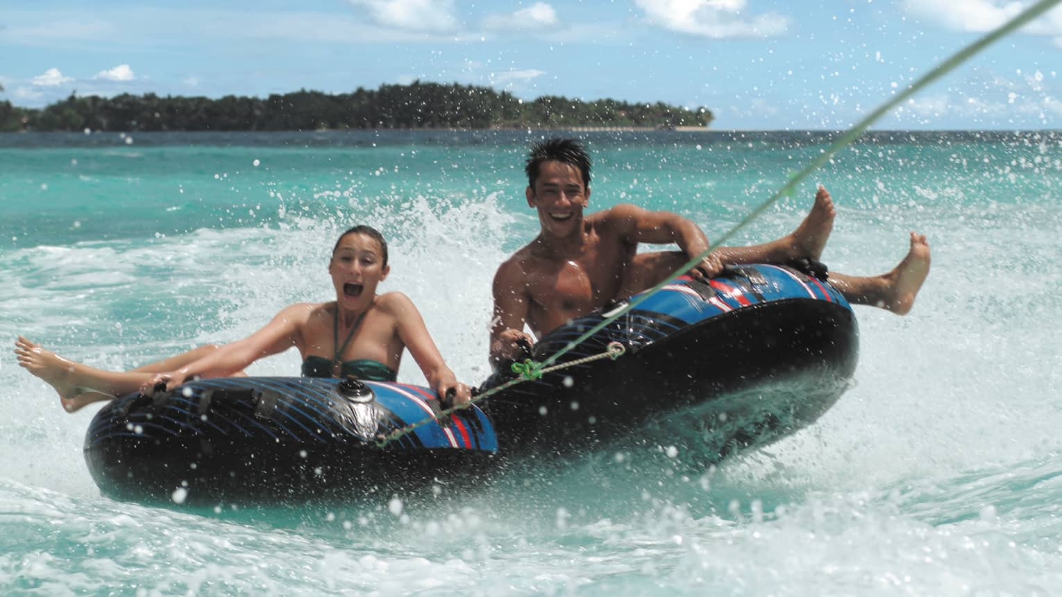 Laughing man and woman hold onto inflatable inner tubes as they ride on ocean