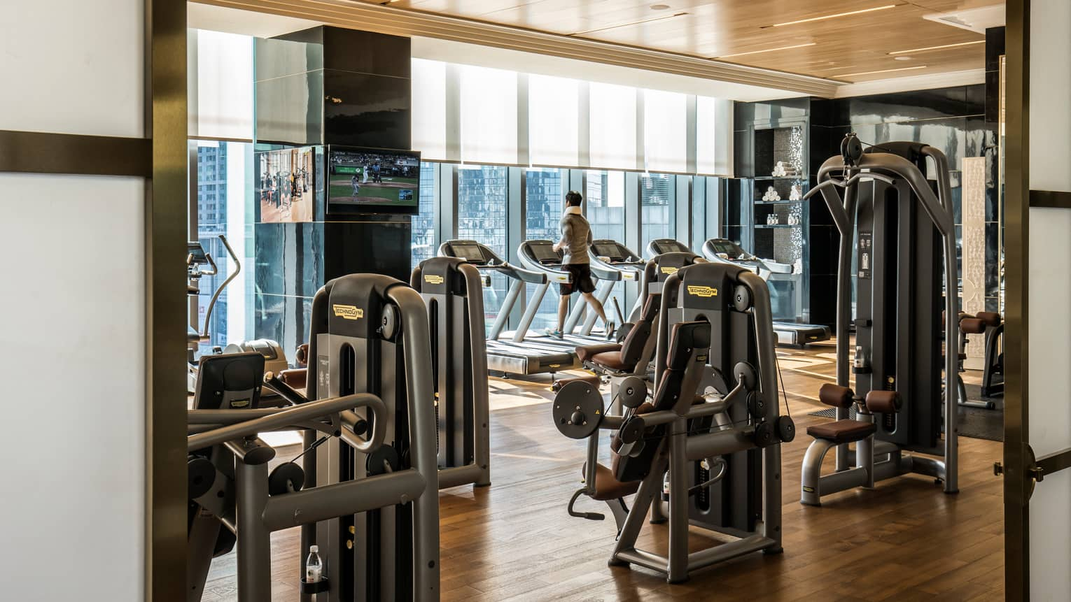 Man runs on treadmill in Fitness Centre by cardio machines, window