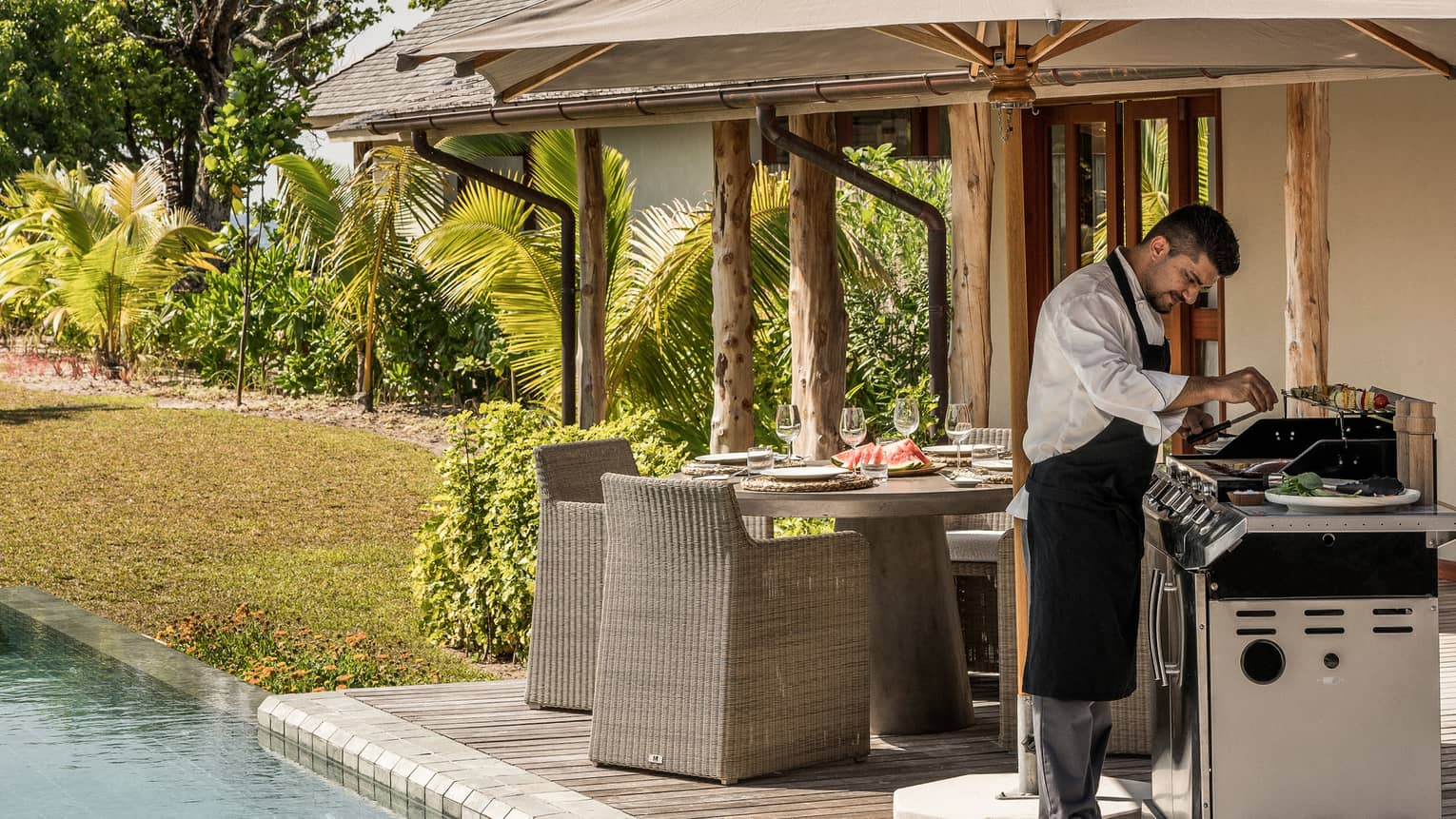 Chef wearing apron cooks at barbecue on deck by dining table, pool
