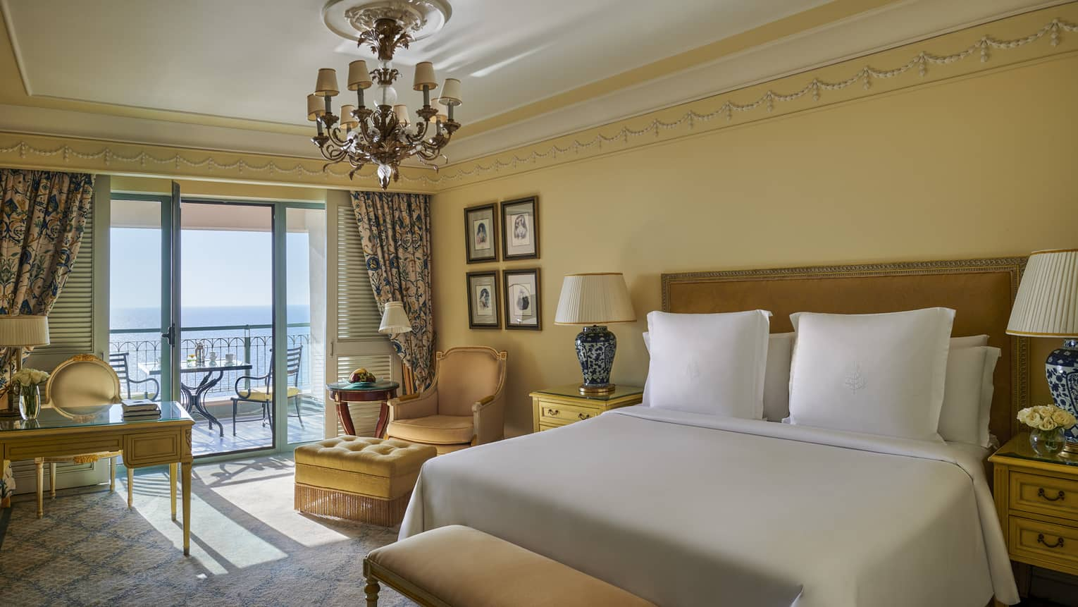 Elegant suite with vintage furniture, drapes framing window leading to balcony and sea views