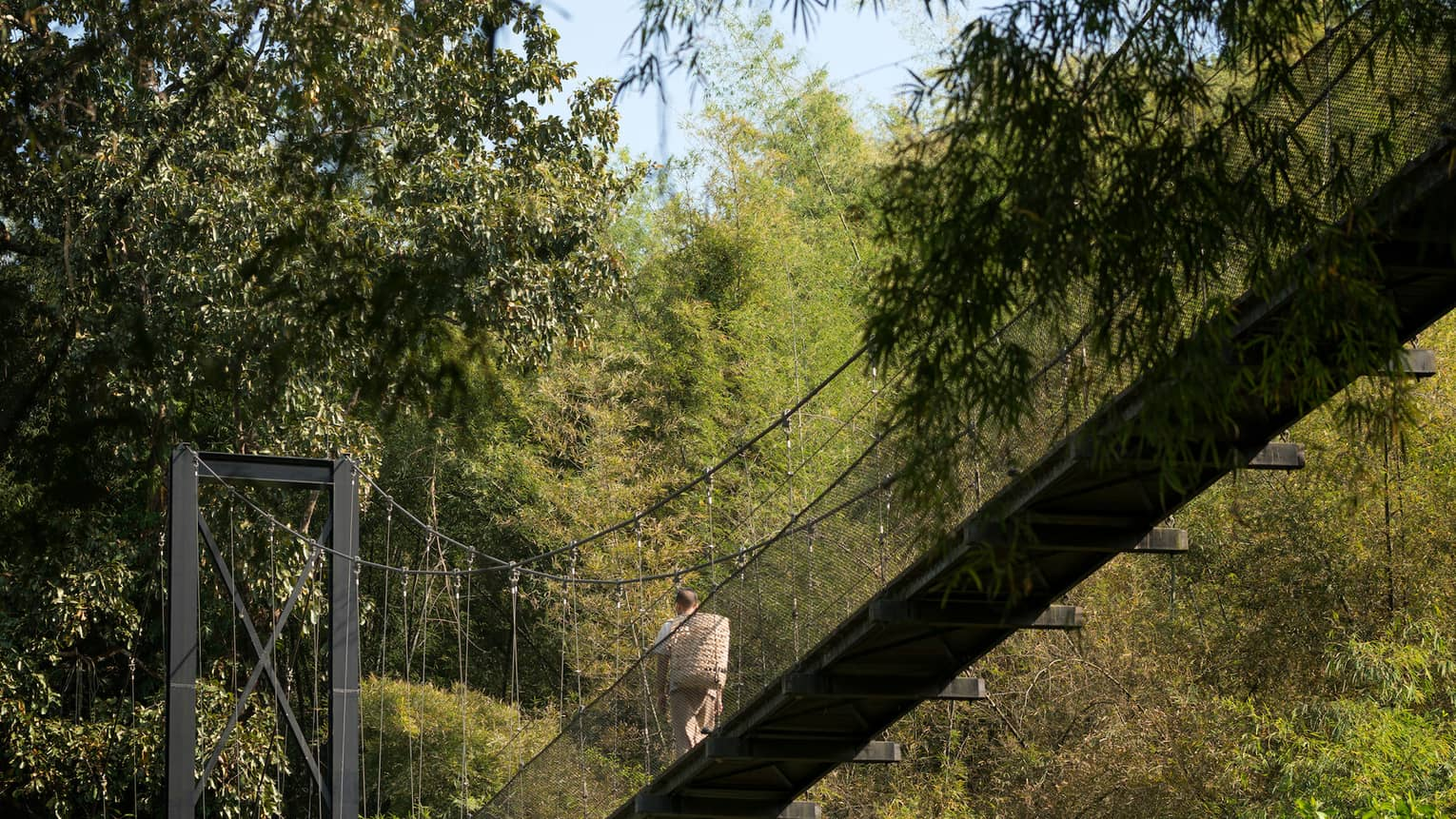 Man with woven basket on back walks across suspension bridge over tropical trees