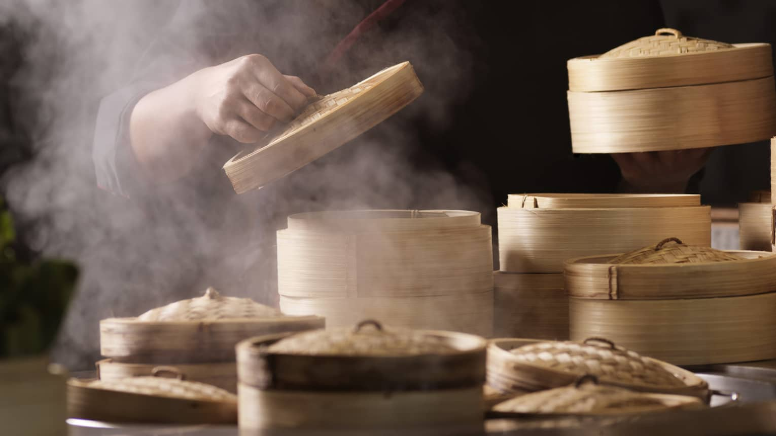 Man lifts top of bamboo steamer, steam rises at Sintoho Dim Sum Station