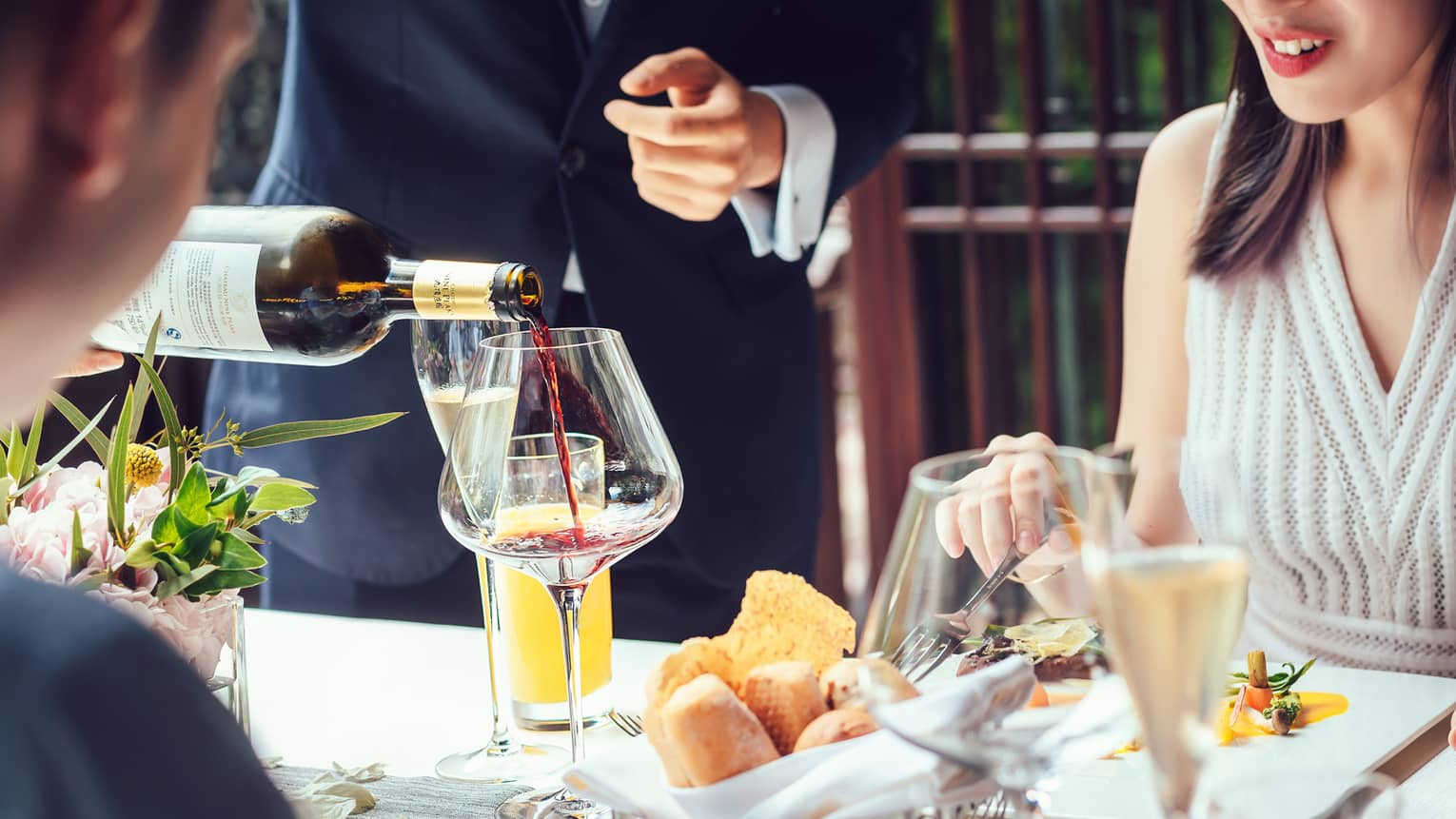 Server pouring red wine into large glass as couple dines at table