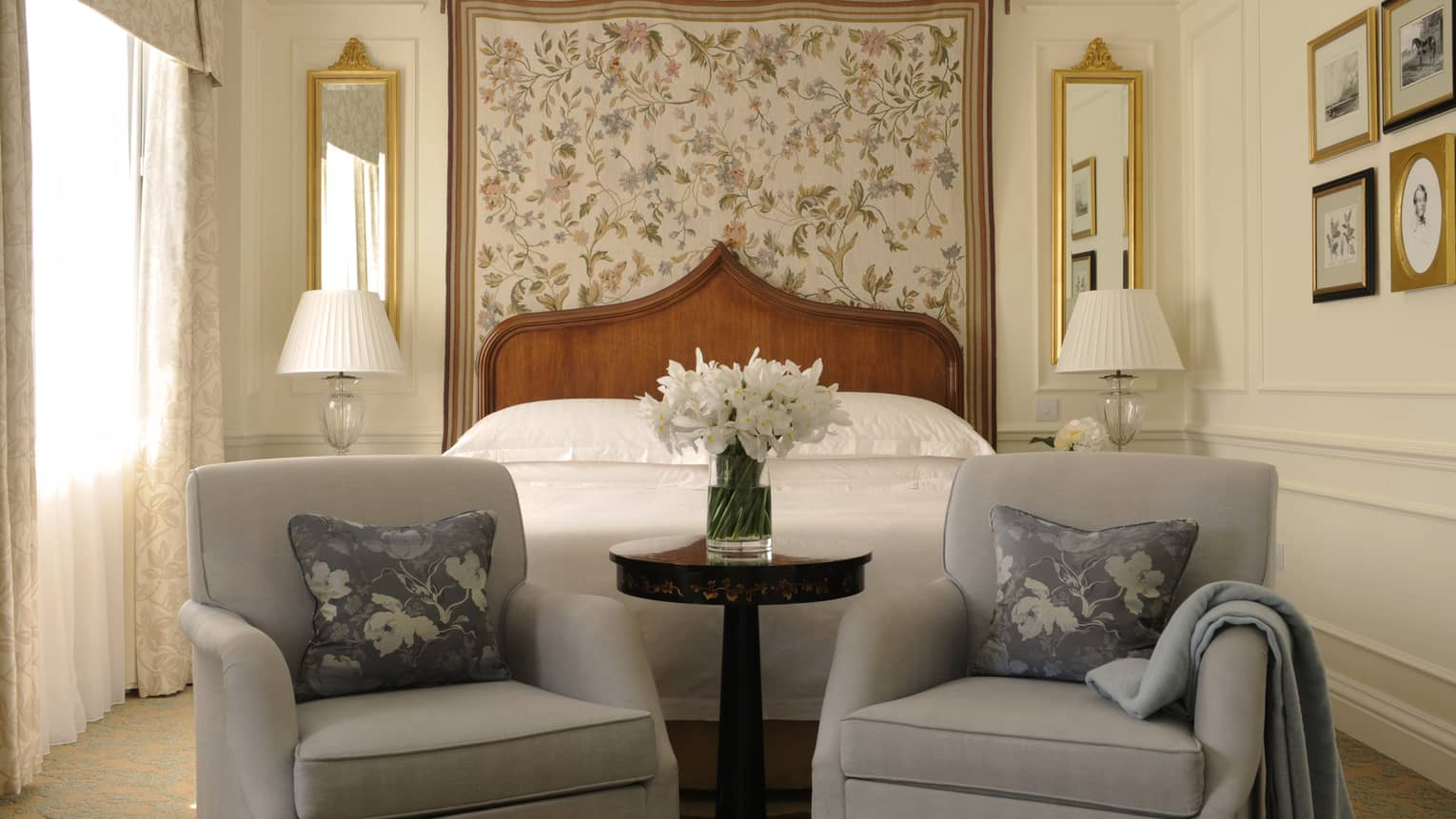 Two plush armchairs, fresh white flowers at foot of hotel bed, floral headboard