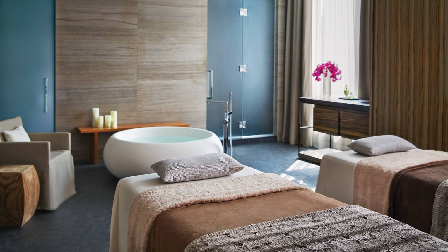 Couples massage bed side-by-side in spa room by round tub, armchair