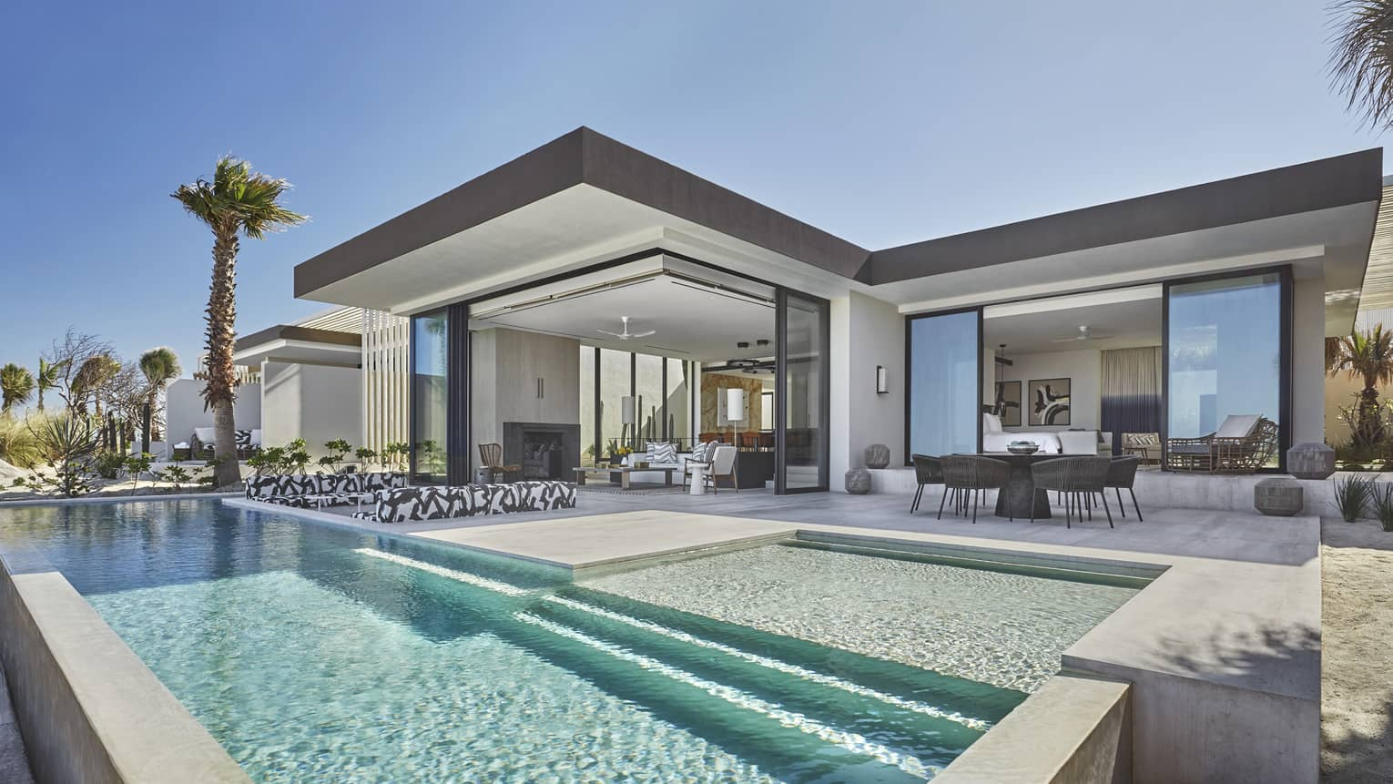 Modern outdoor terrace of presidential suite, dining table, long rectangular pool