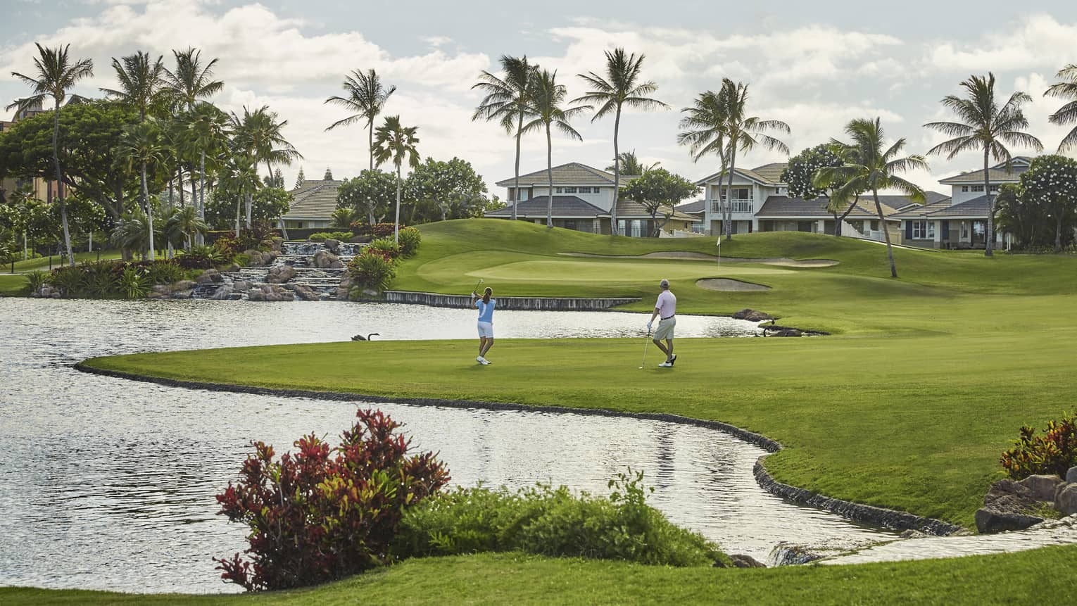 Woman swings golf club as man watches on Ko Olina Golf Club green by water, houses