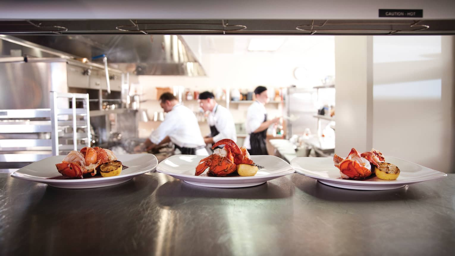 Three white plates with whole lobsters, lemons on kitchen lines, chefs in background