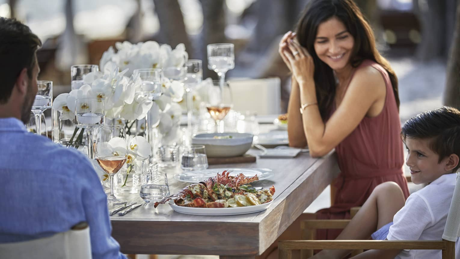 Smiling couple with young son at dining table with seafood, wine, white flowers