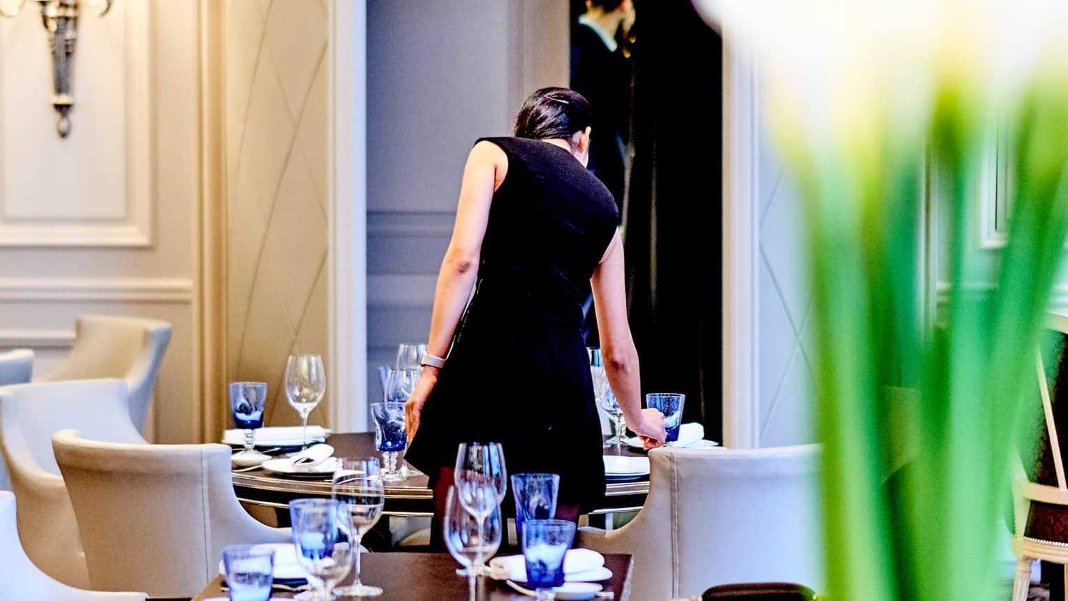 Back of woman wearing black dress standing over Le George dining table