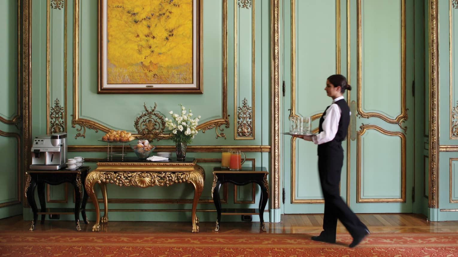 Server in black vest, pants carries tray down historic hallway with gold trim, table