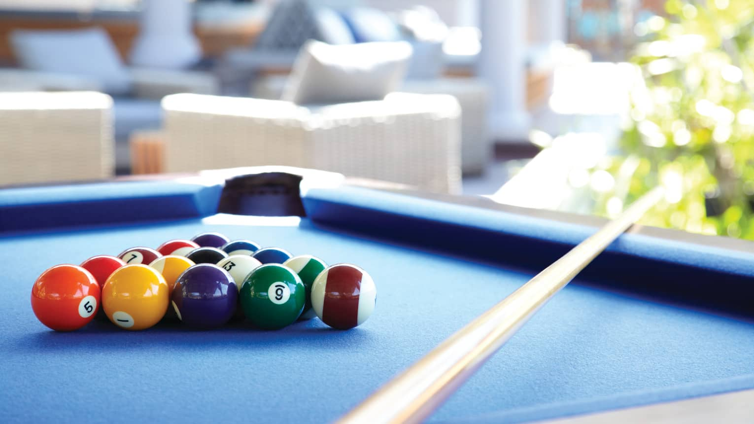 Billiards balls gathered in triangle on pool blue table, cue resting on corner