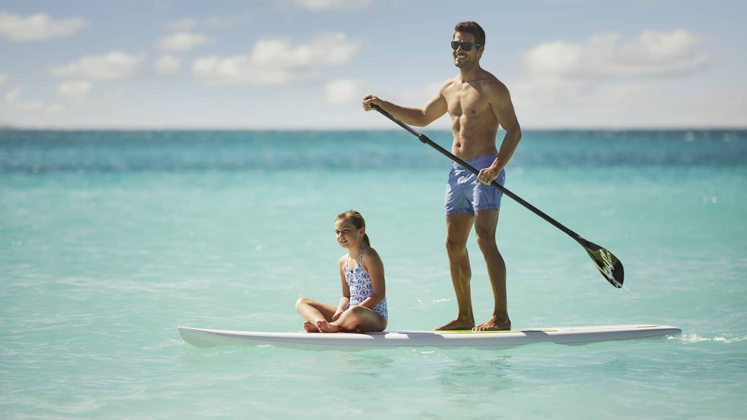 Man stands on paddleboard holding paddle as young girl in swimsuit sits cross-legged on board