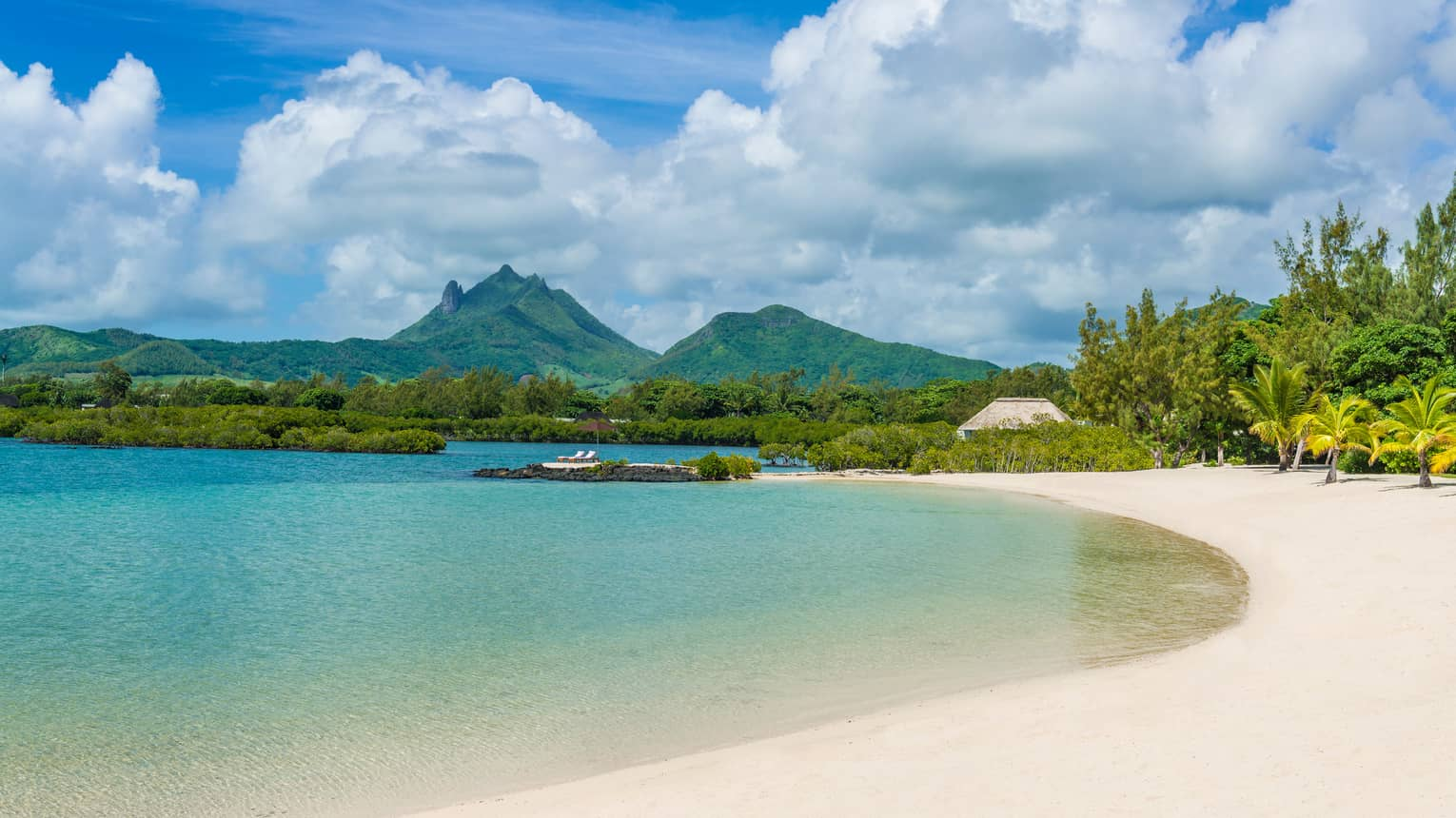 Mauritius green mountains, tropical forest behind white sand beach