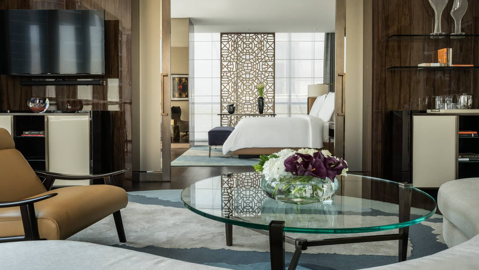 Four Seasons Deluxe Executive Suite living room with round glass coffee table, door to bedroom