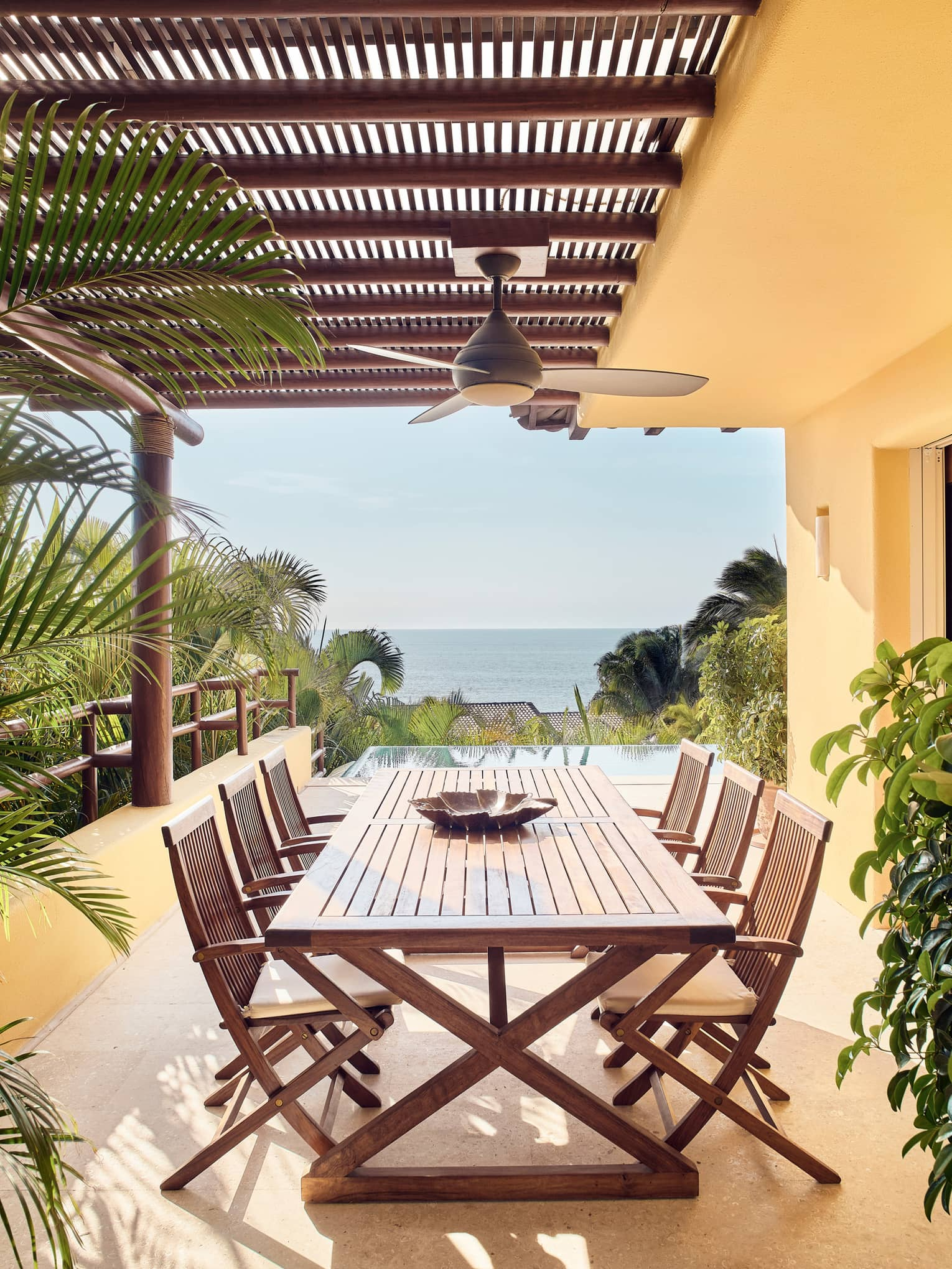 Wood patio table, chairs under pergola and ceiling fan, ocean views