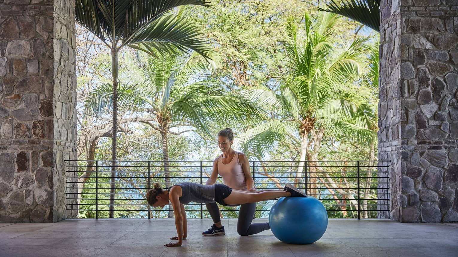 Trainer helps woman balance legs on blue pilates ball in stone fitness centre
