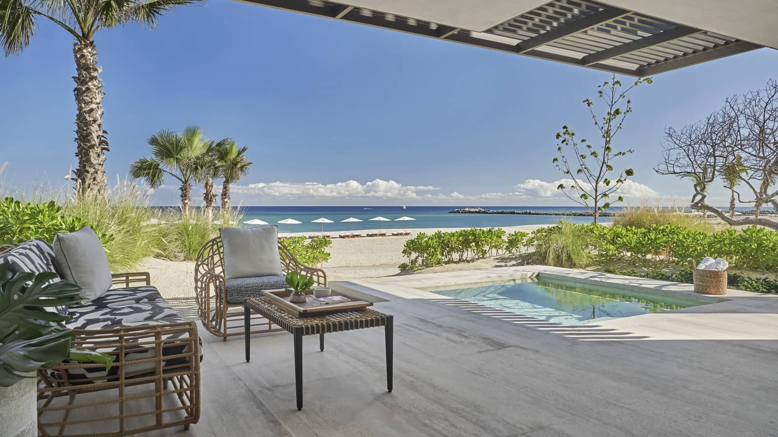 Outdoor terrace with beach and ocean view, small pool, two arm chairs and table