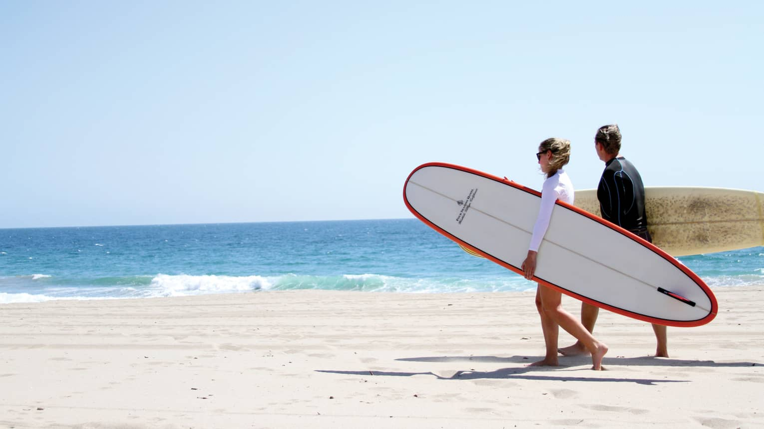 A couple on the beach holding surfboards under their arms.