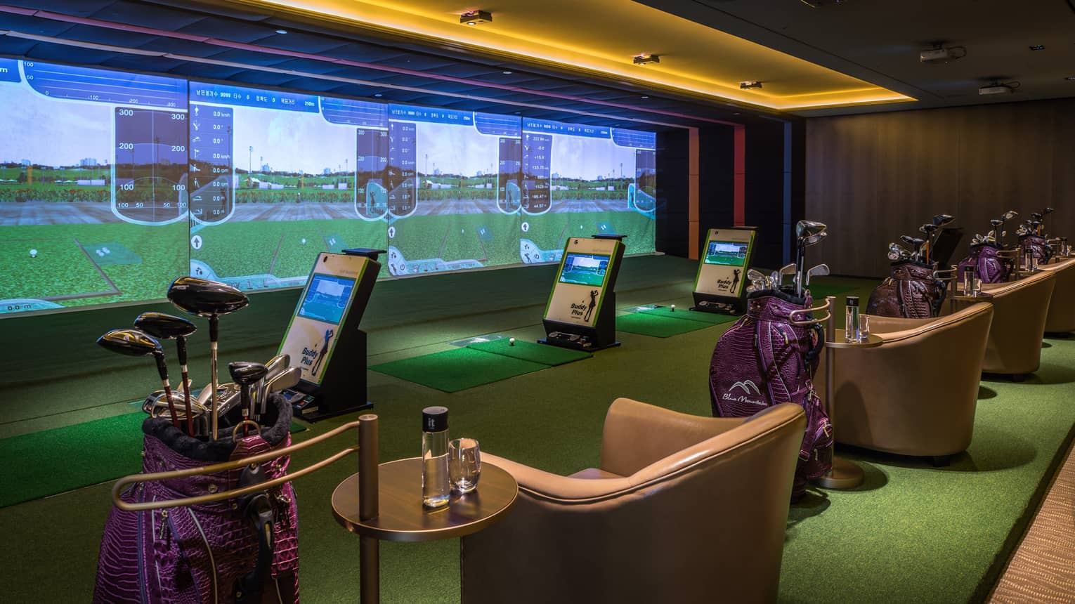 Wall with animated screens, 3D golf course game centre, armchairs with water bottles