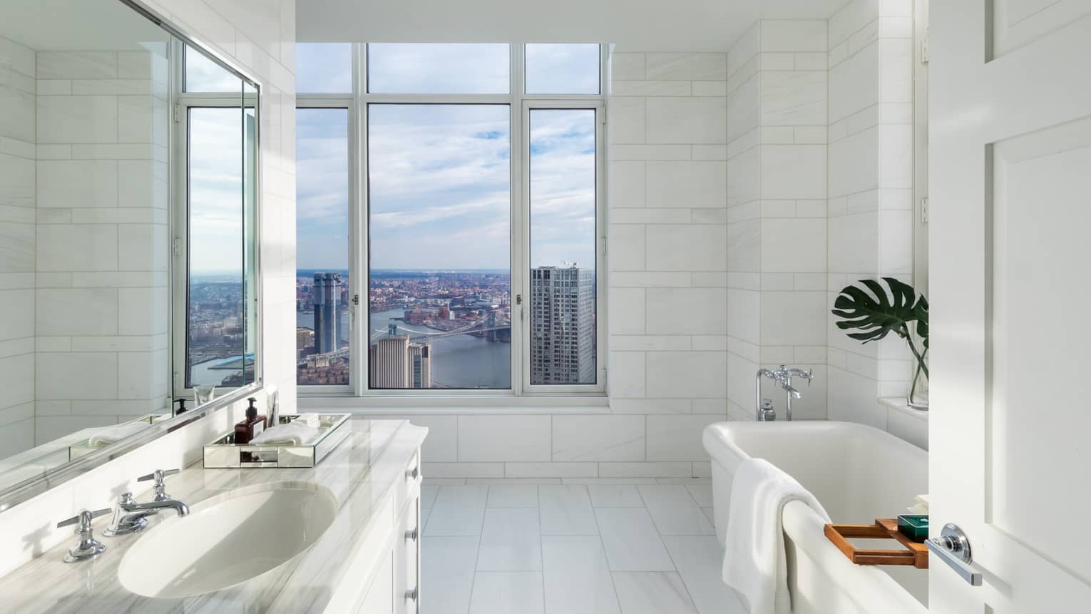 White marble bathroom, vanity, towel over tub by large picture window