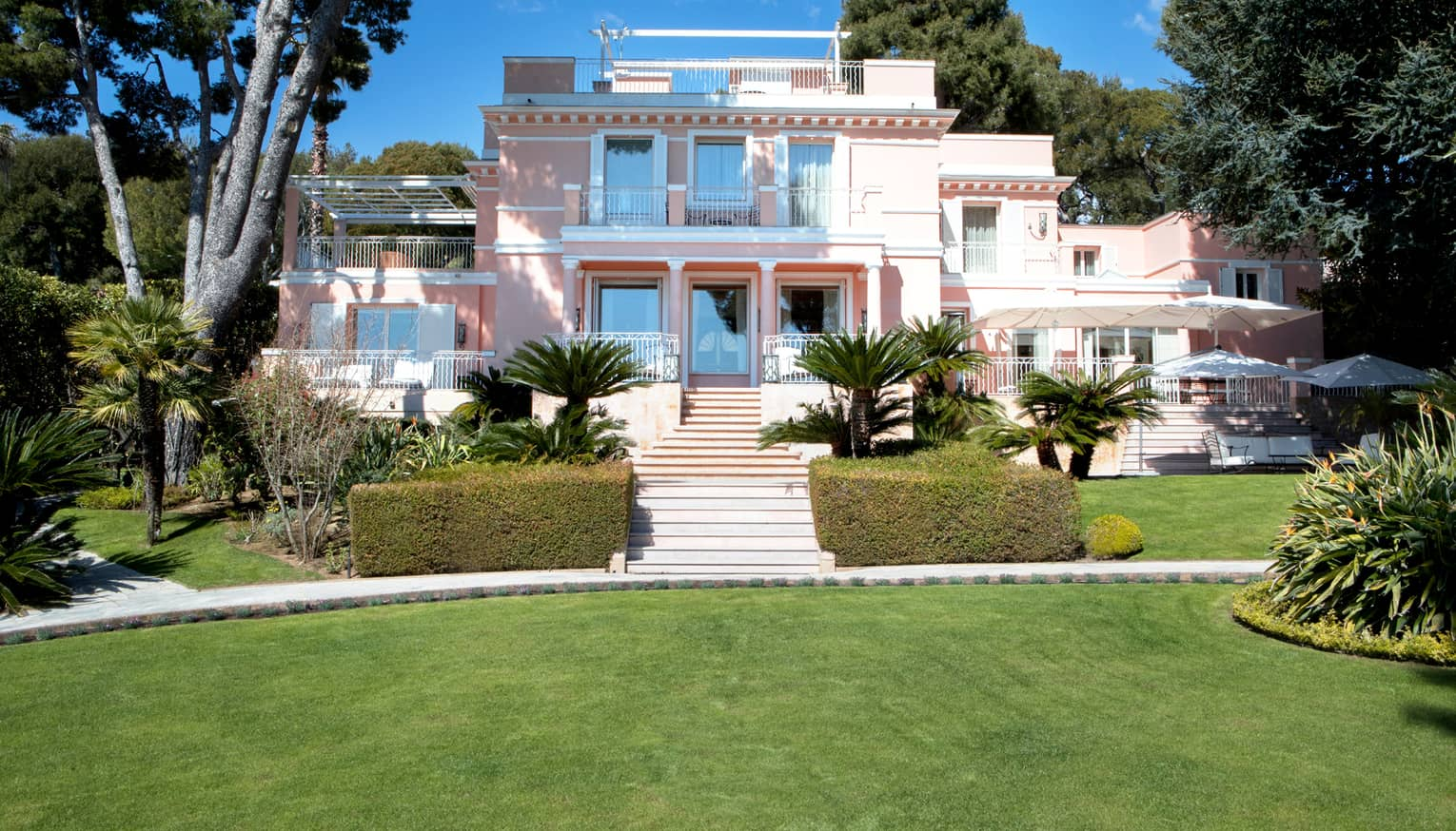 Manicured gardens, steps up to large three-storey pink Villa Rose-Pierre