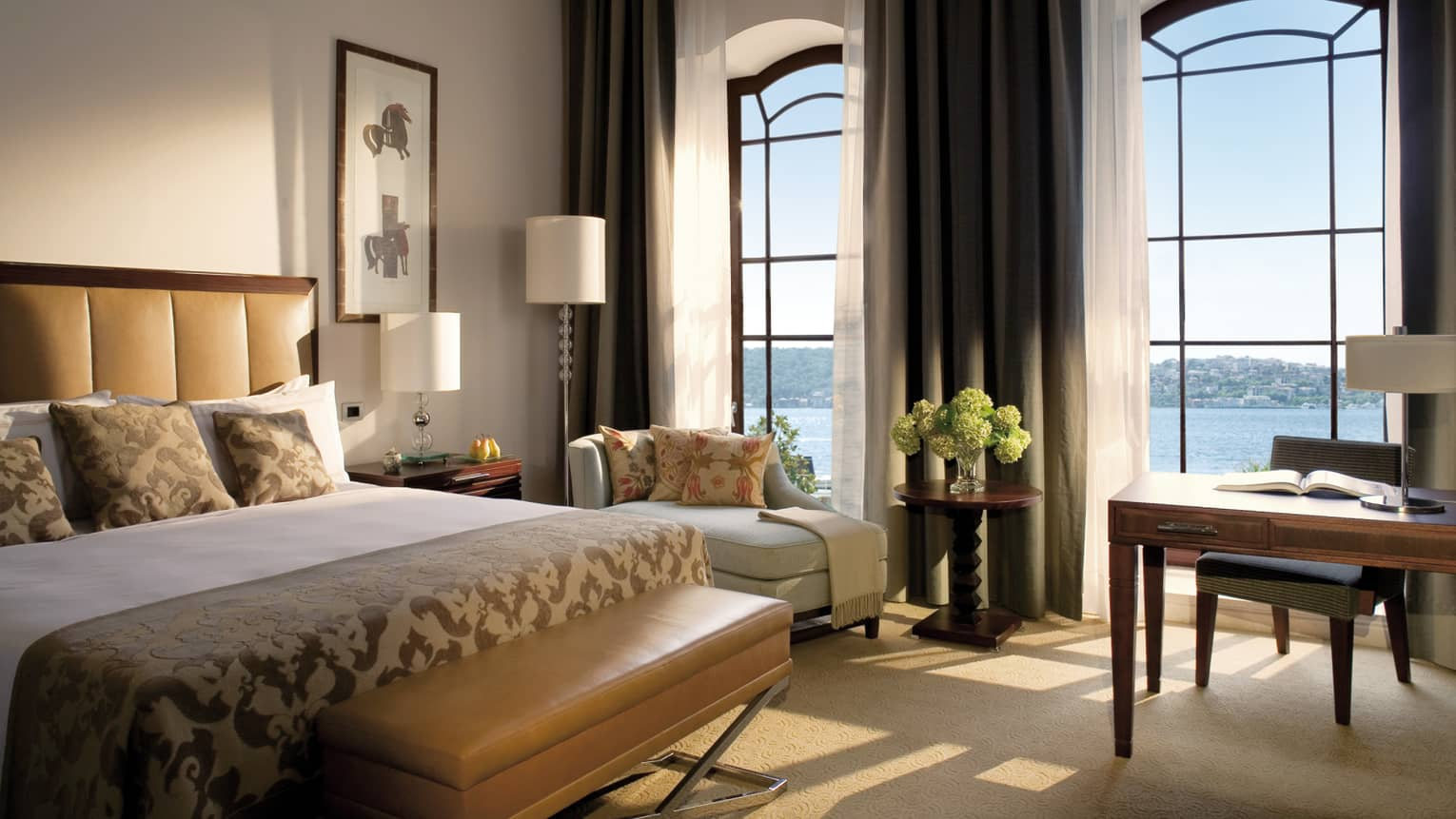 The Palace Bosphorus Room bed with padded brown headboard, bench, sunny bay windows with sea views