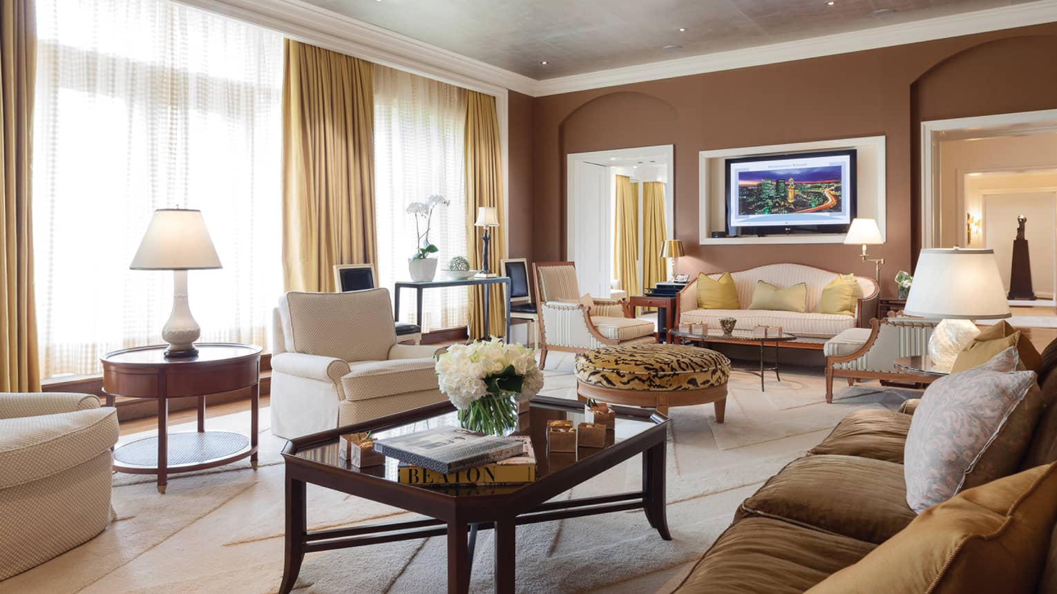 Presidential Suite living area coffee table with books and fresh white flowers, white armchair, tiger-print ottoman, sofas