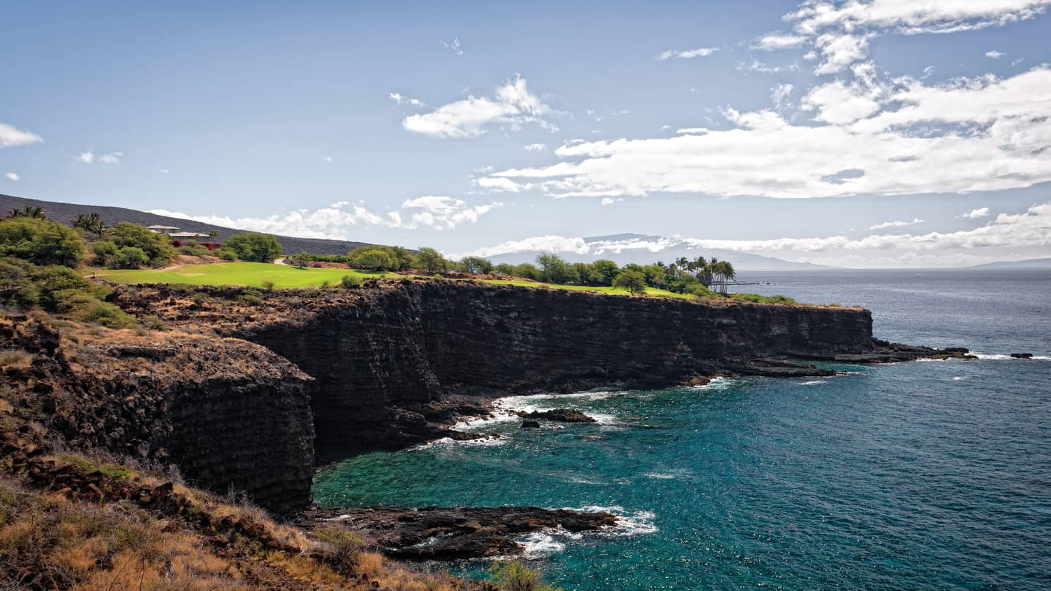 Sweeping view of Manele Golf Course on high cliffs over ocean