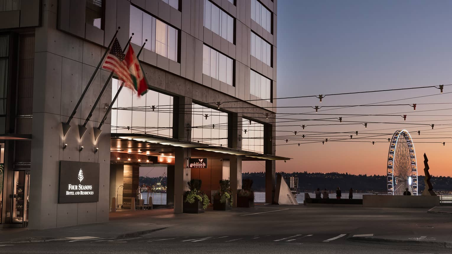 Four Seasons hotel exterior, front entrance with the Seattle Great Wheel in background at sunset