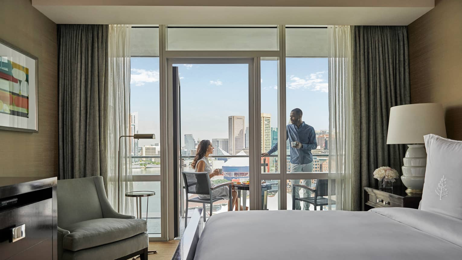 Hotel room with king bed, light grey arm chair, opening to outdoor balcony with two people talking