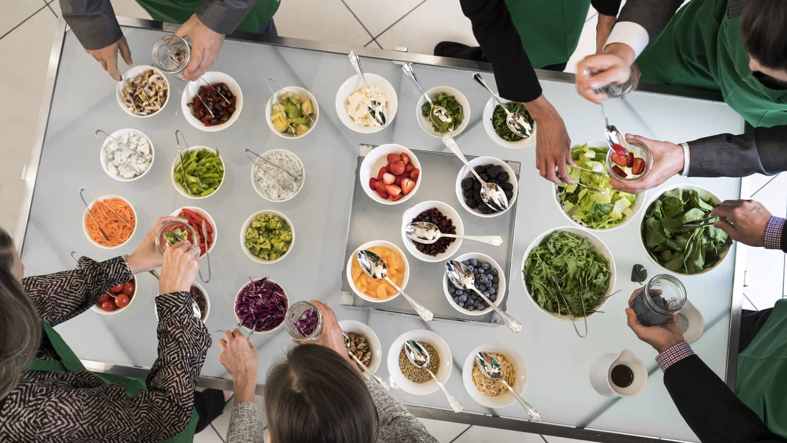 Aerial view of people gathered around buffet table salad bar with small bowls of fruit, vegetables