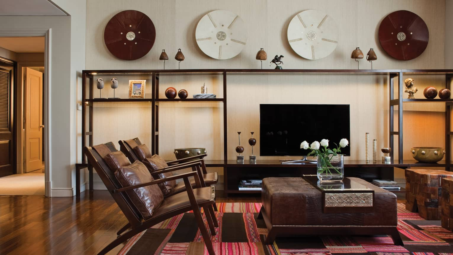 Modern brown leather armchairs and large ottoman with fresh flowers, modern and wood Argentine-inspired art