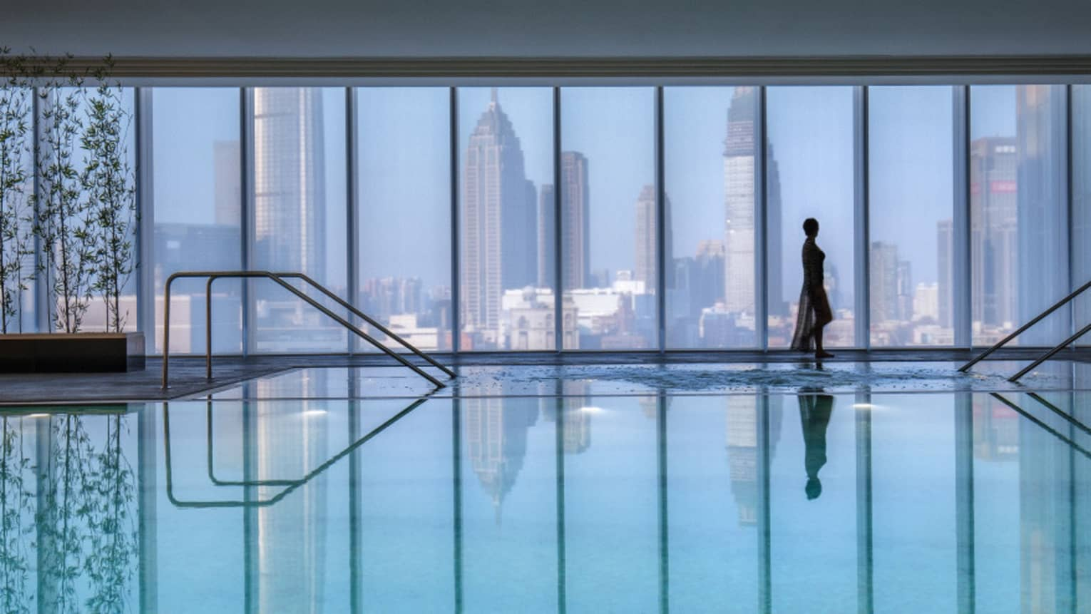 Silhouette of woman walking by blue indoor swimming pool, floor-to-ceiling window